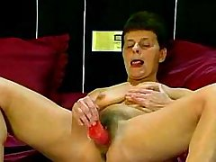 Horny old slut masturbates with big dildo in bed