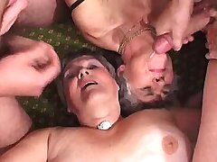 Two lewd grannies fuck from behind and get facials